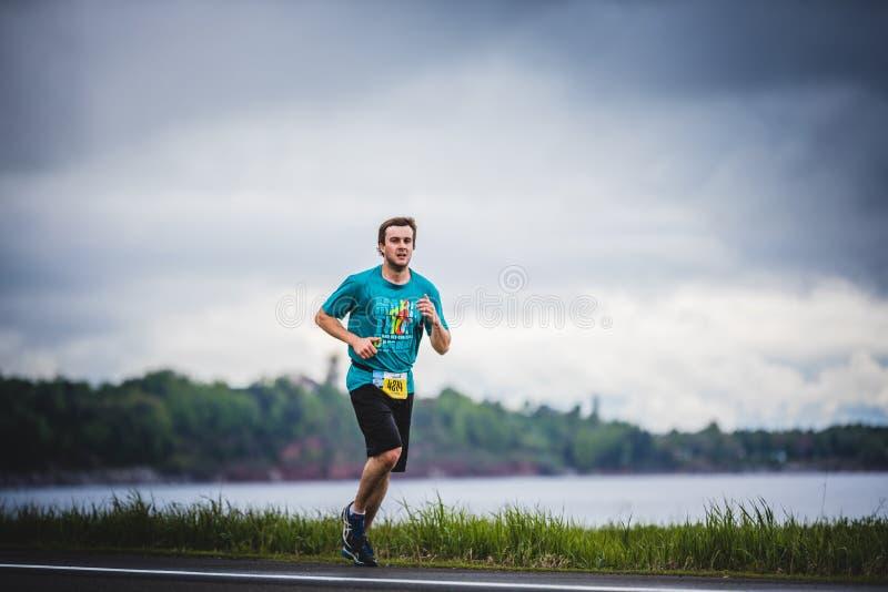 Junger Mann Marathoner an ungefähr 7km des Abstandes allein auf der Seite lizenzfreie stockfotos