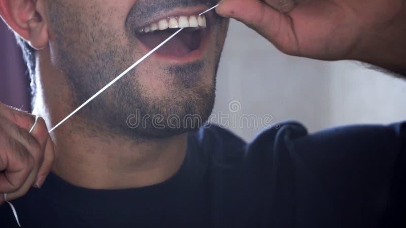 Junger Mann mit Bart benutzt Zahnseide, um seine Zähne zu säubern Nahaufnahme des Mannes flossing seine Zähne Mundgesundheitswese lizenzfreie stockfotos