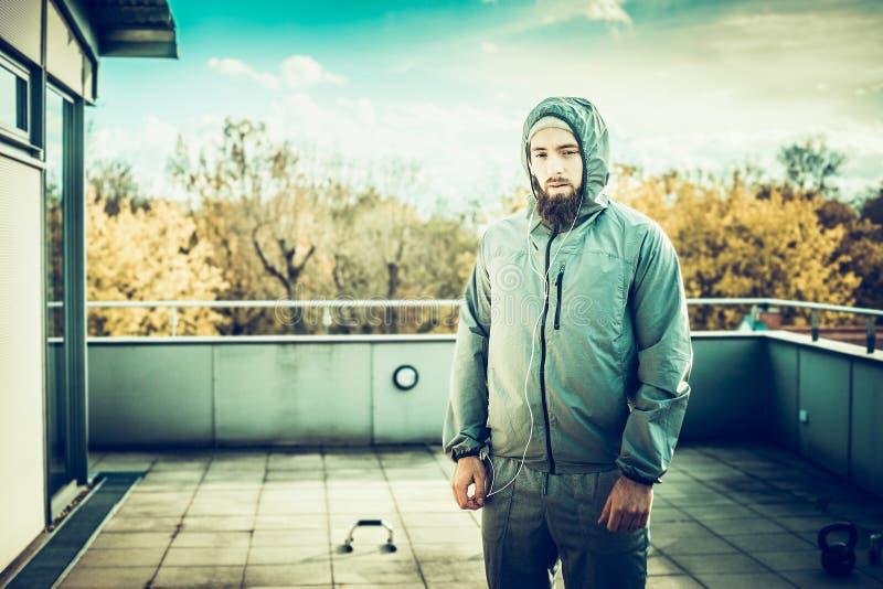 Junger Mann mit Bart in einer Sportklage, stehend auf der Terrasse des Hauses, auf der Hintergrundsportausrüstung und die Art lizenzfreie stockfotos