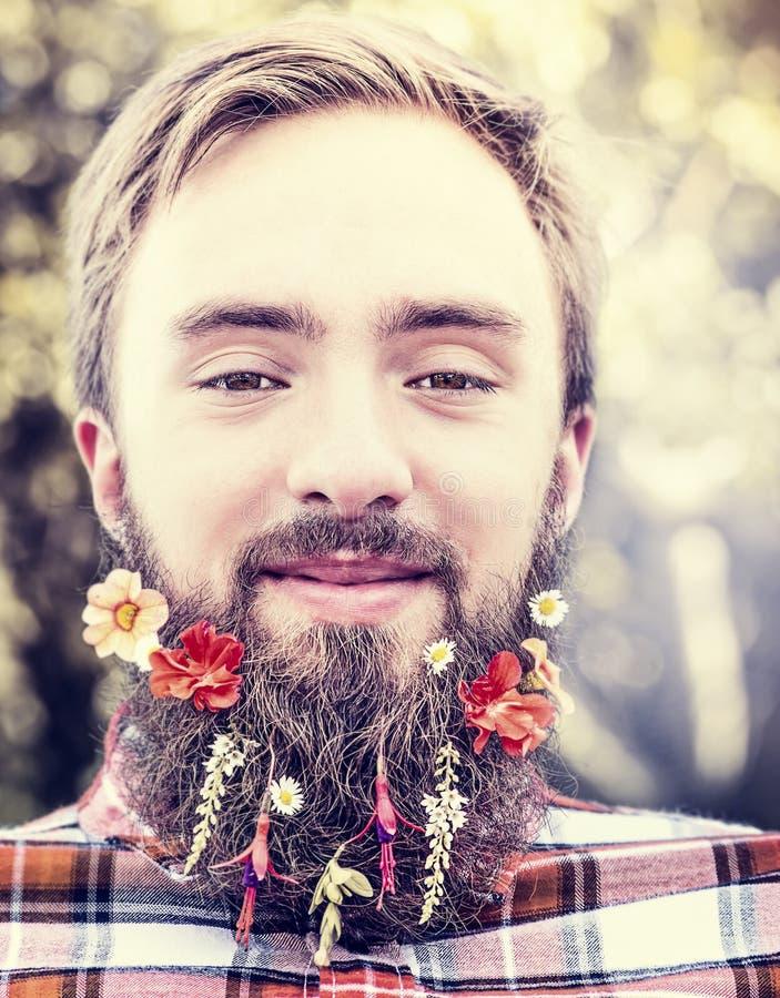 Junger Mann mit Blumen in seinem natürlicher unscharfer Hintergrundabschluß des Bartes oben stockbilder