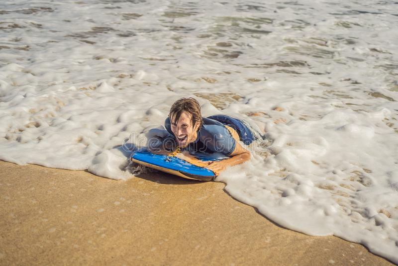 Junger Mann mit Boogie-Brett am Strand stockfotografie