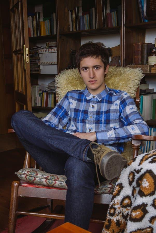 Junger Mann mit dem karierten Hemd und Jeans, die an sitzen lizenzfreie stockfotos