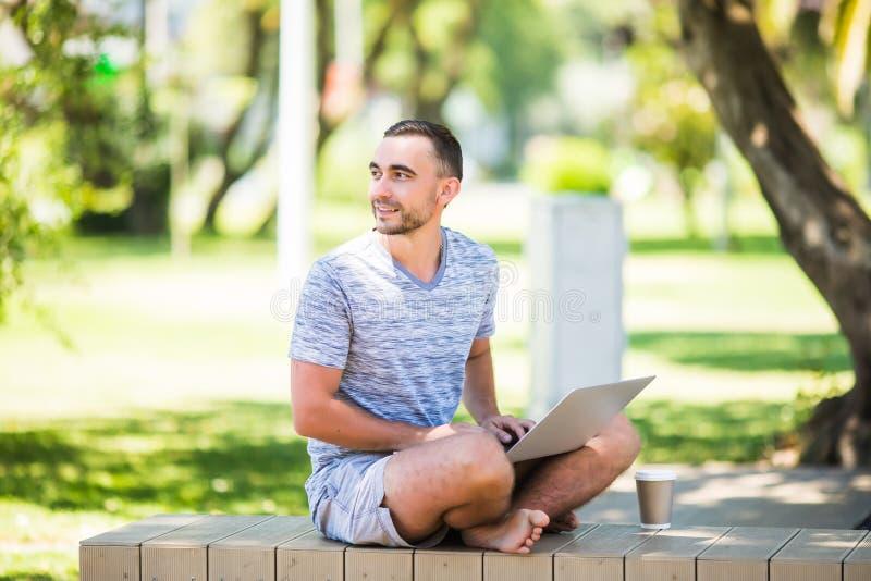 Junger Mann mit dem Laptop, der auf einer Holzbank im Park sitzt stockbilder