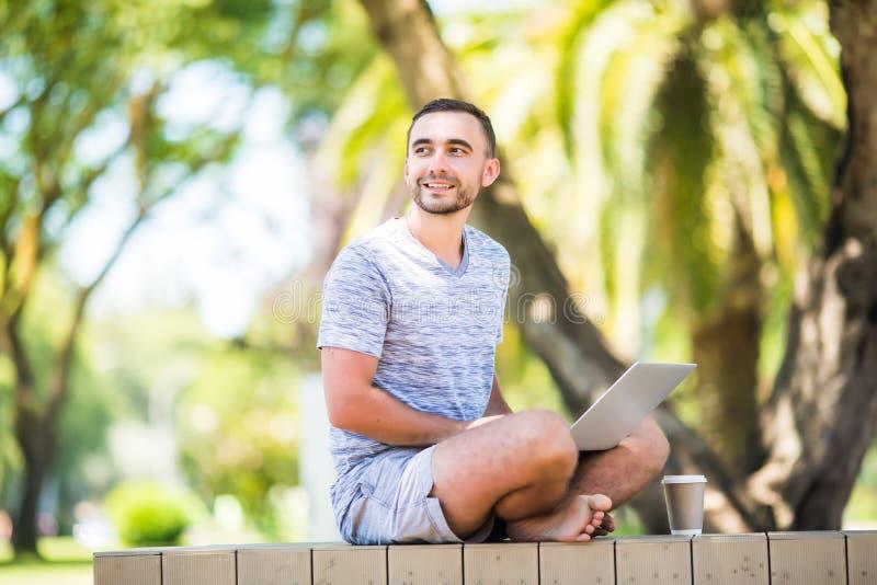 Junger Mann mit dem Laptop, der auf einer Holzbank im Park sitzt stockfotos