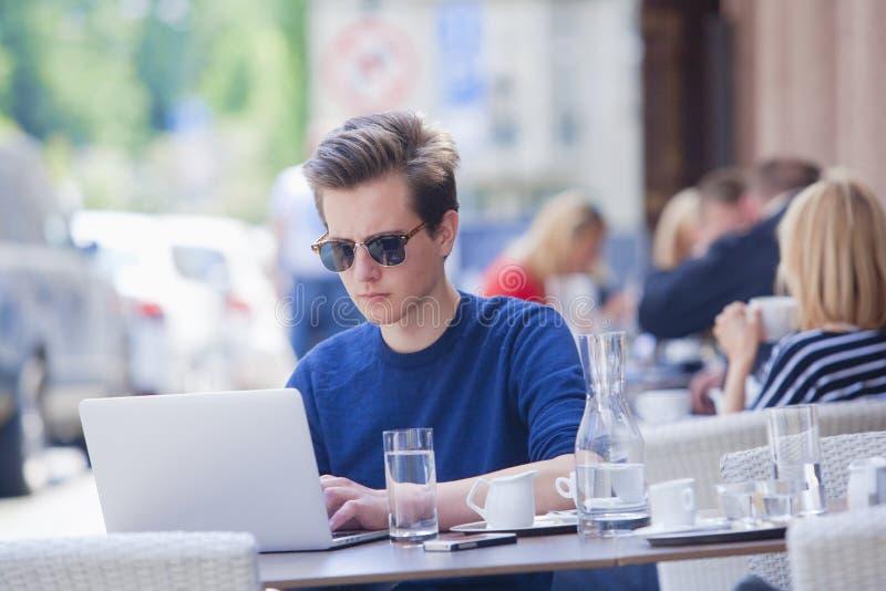 Junger Mann mit dem Laptop, der im äußeren Café sitzt stockfotografie