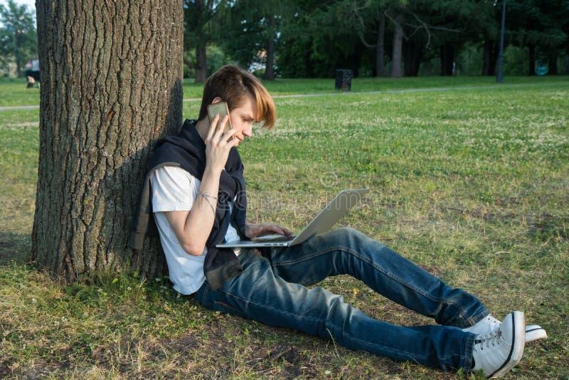 Junger Mann mit dem Laptop und Kopfhörern, die im Park nahe Bürogebäude arbeiten lizenzfreies stockbild