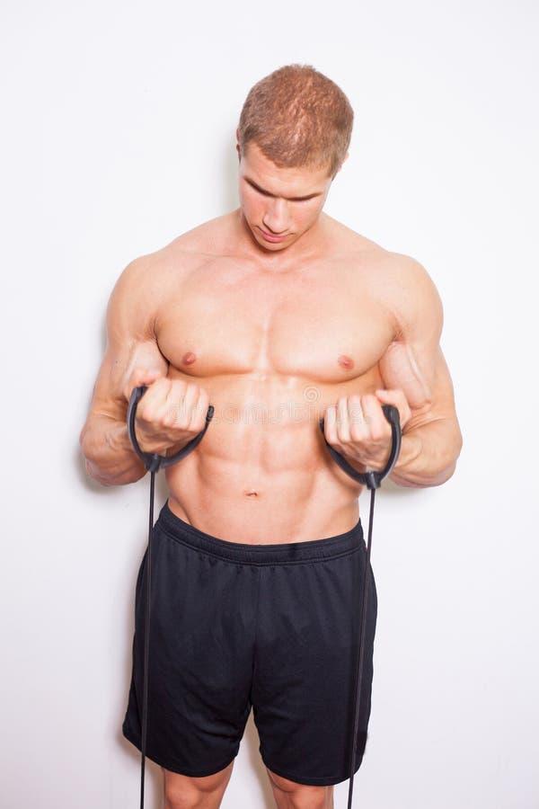 Junger Mann mit dem muskulösen Körper, der Eignungsübung tut. Ohne shi stockbild