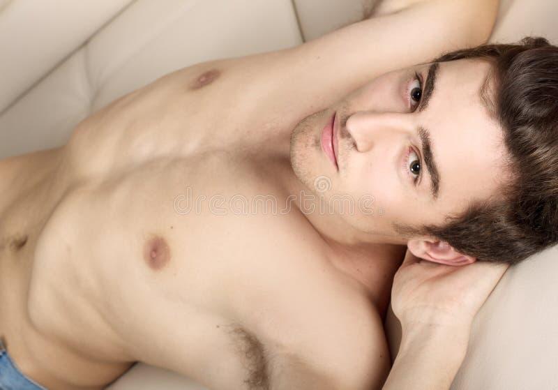 Junger Mann mit dem nackten Torso, der auf einer weißen Couch liegt stockbilder