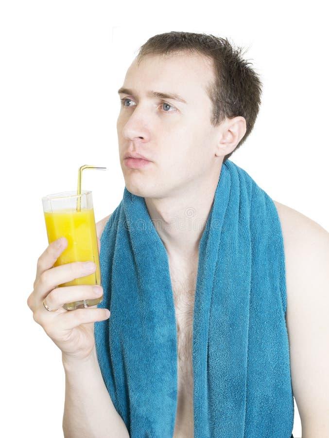 Junger Mann mit dem Orangensaft getrennt auf Weiß stockfotografie