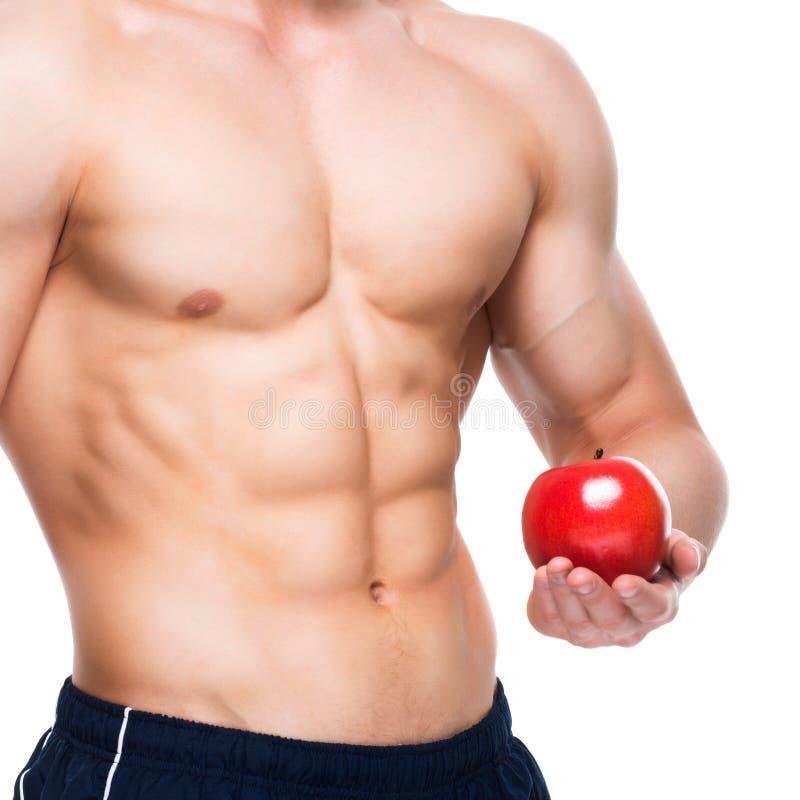 Junger Mann mit dem perfekten Körper, der roten Apfel hält lizenzfreie stockfotos