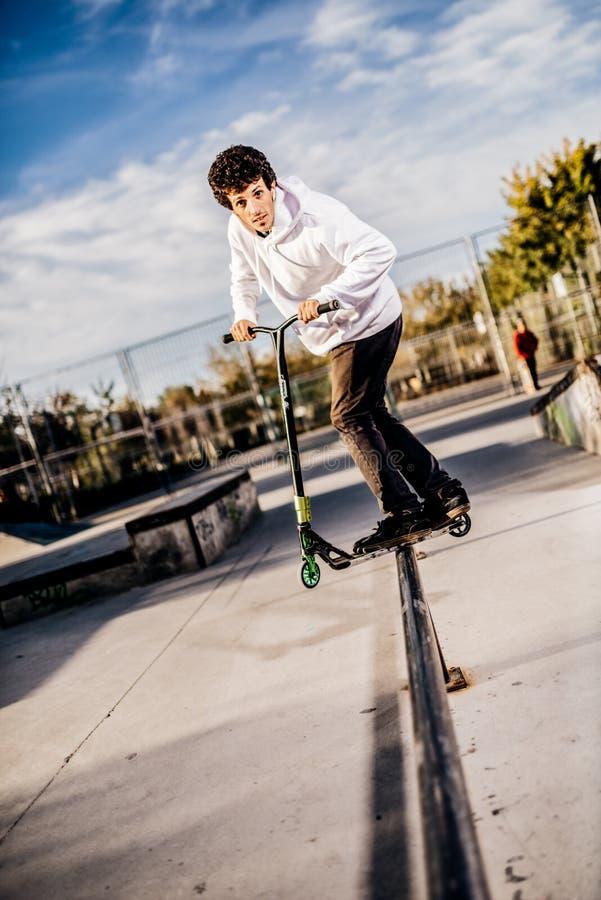 Junger Mann mit dem Roller, der ein Schleifen auf Skatepark macht stockfoto