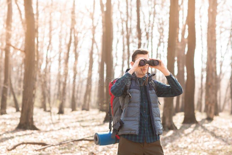 Junger Mann mit dem Rucksack, der die Ferngläser, wandernd im Wald betrachtet lizenzfreie stockbilder