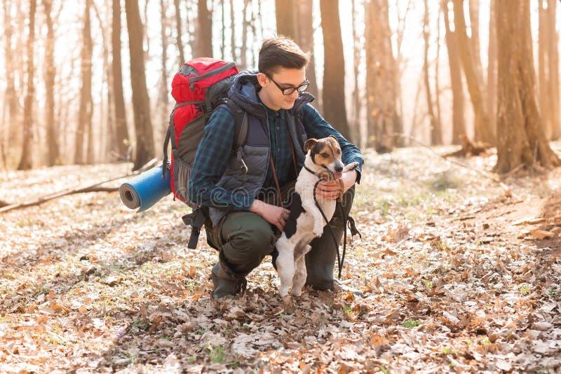 Junger Mann mit dem Rucksack, der im Wald mit seinem Hund wandert Natur und Konzept der körperlichen Bewegung lizenzfreies stockfoto
