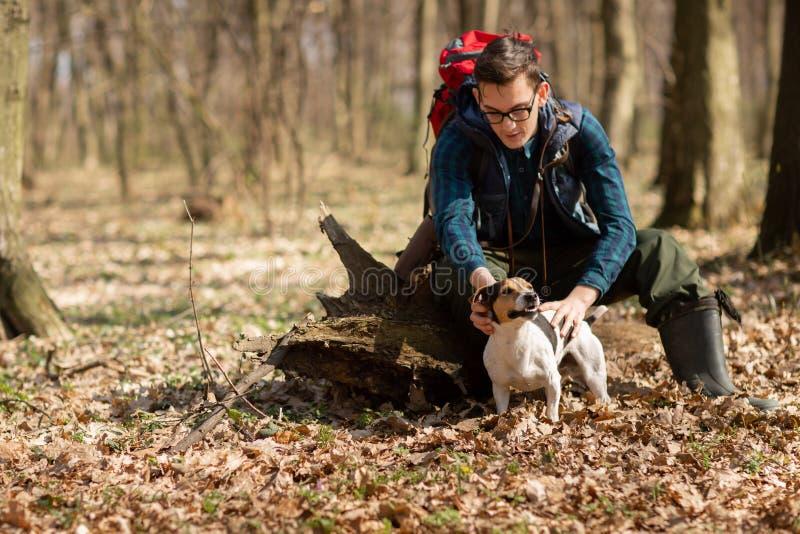 Junger Mann mit dem Rucksack, der im Wald mit seinem Hund wandert Natur und Konzept der k?rperlichen Bewegung lizenzfreie stockfotografie