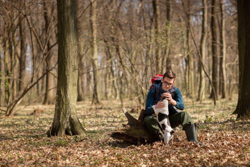 Junger Mann mit dem Rucksack, der im Wald mit seinem Hund wandert Natur und Konzept der k?rperlichen Bewegung stockbilder