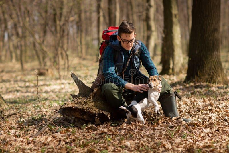Junger Mann mit dem Rucksack, der im Wald mit seinem Hund wandert Natur und Konzept der k?rperlichen Bewegung lizenzfreie stockfotos