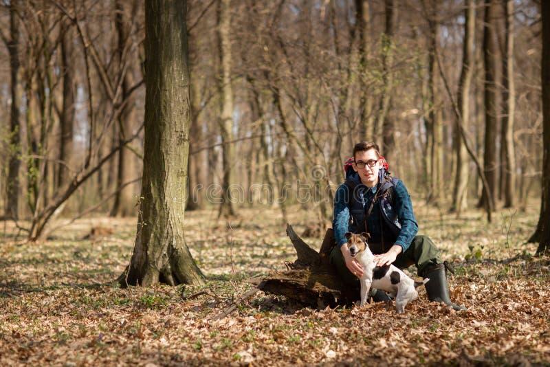 Junger Mann mit dem Rucksack, der im Wald mit seinem Hund wandert Natur und Konzept der k?rperlichen Bewegung stockfotografie