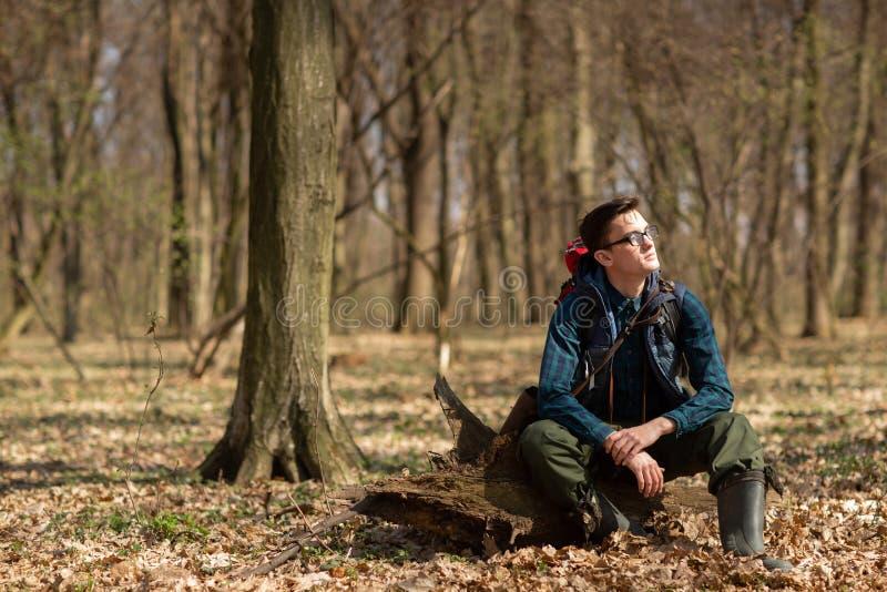 Junger Mann mit dem Rucksack, der in der Waldnatur und dem Konzept der körperlichen Bewegung wandert stockbild