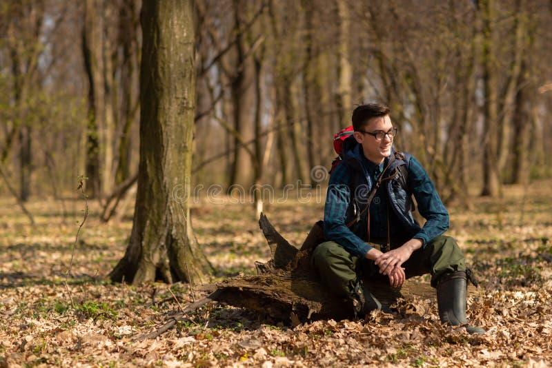 Junger Mann mit dem Rucksack, der in der Waldnatur und dem Konzept der k?rperlichen Bewegung wandert lizenzfreies stockfoto
