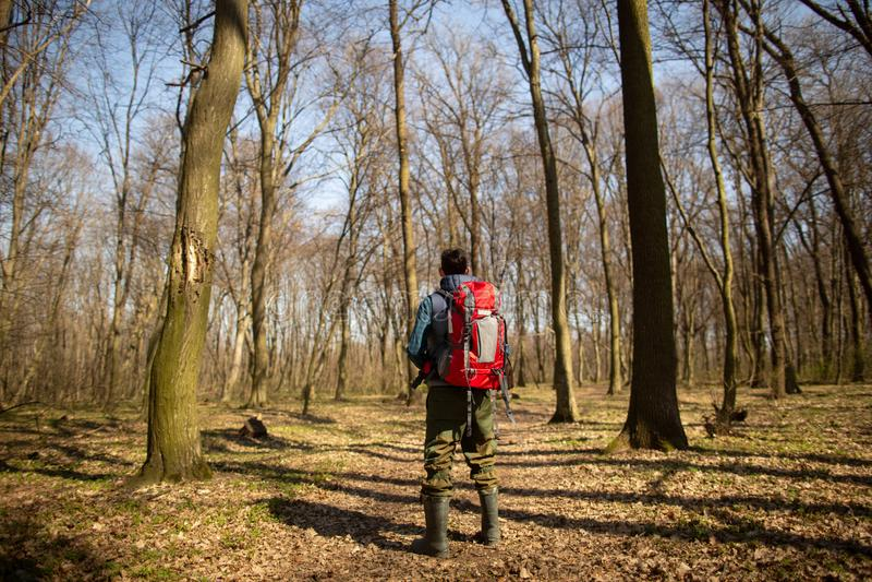 Junger Mann mit dem Rucksack, der in der Waldnatur und dem Konzept der k?rperlichen Bewegung wandert stockfoto
