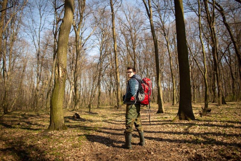 Junger Mann mit dem Rucksack, der in der Waldnatur und dem Konzept der k?rperlichen Bewegung wandert lizenzfreie stockfotos