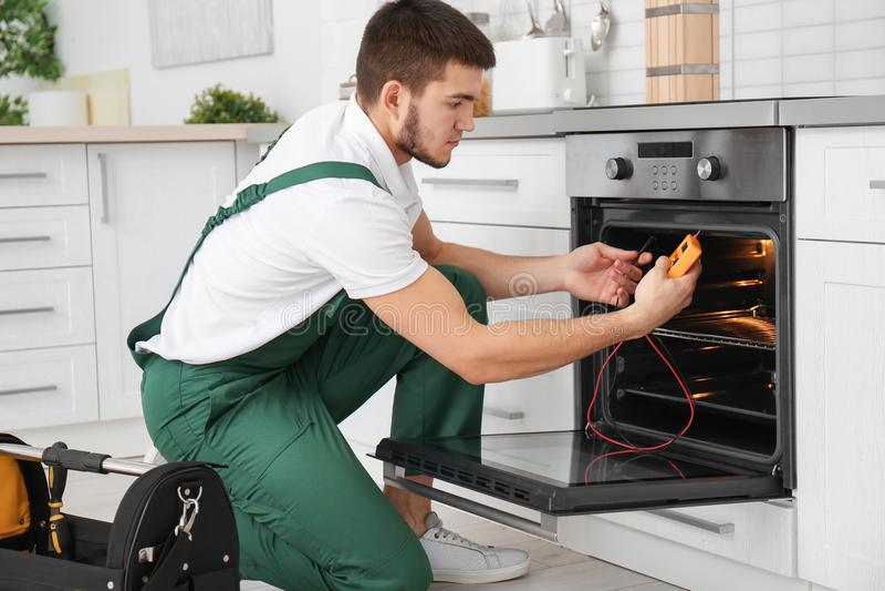Junger Mann mit dem Vielfachmessgerät, das Ofen repariert lizenzfreie stockfotografie
