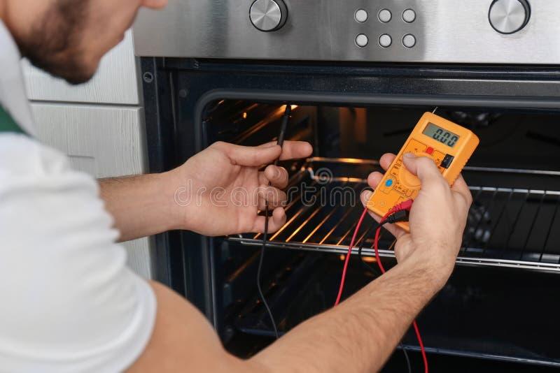 Junger Mann mit dem Vielfachmessgerät, das Ofen repariert, stockbild