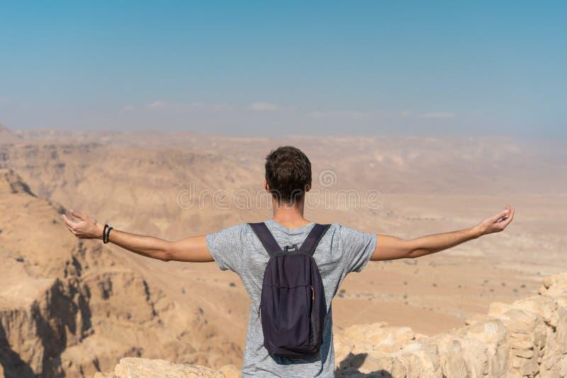 Junger Mann mit den Armen angehoben, das Panorama über der Wüste in Israel schauend stockbilder
