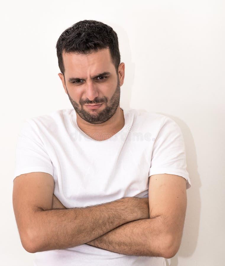 Junger Mann mit den gefalteten Händen, schaut verärgert lizenzfreies stockbild