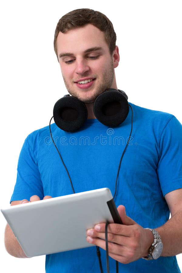 Junger Mann mit den Kopfhörern, die an einem Tablette-PC arbeiten lizenzfreie stockbilder