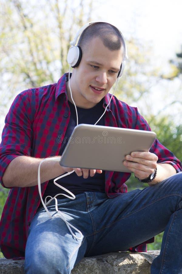Junger Mann mit den Kopfhörern, die, hörend auf Musik und holdin sitzen stockbild