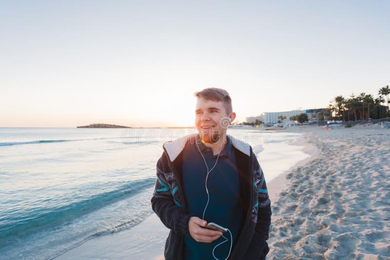 Junger Mann mit den Kopfhörern, die am Strand und am Lächeln stehen stockbilder