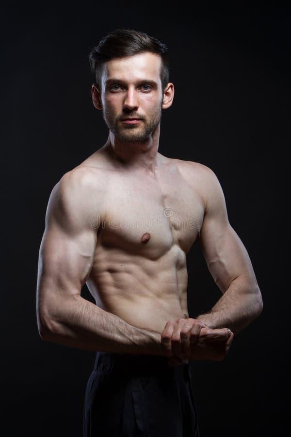 Junger Mann mit den Muskeln, die auf der Kamera ernst auf schwarzem Hintergrund schauen stockfotos