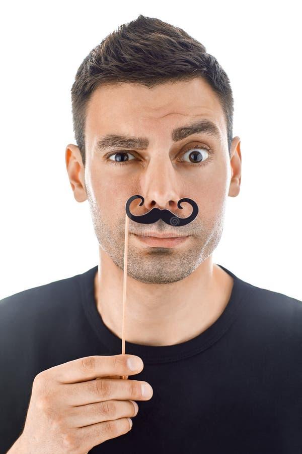 Junger Mann mit den Papierschnurrbärten, welche die Gesichter lokalisiert auf weißem b machen lizenzfreies stockfoto