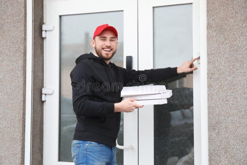 Junger Mann mit den Papppizzakästen, die draußen Türklingel schellen LebensmittelZustelldienst lizenzfreie stockfotografie