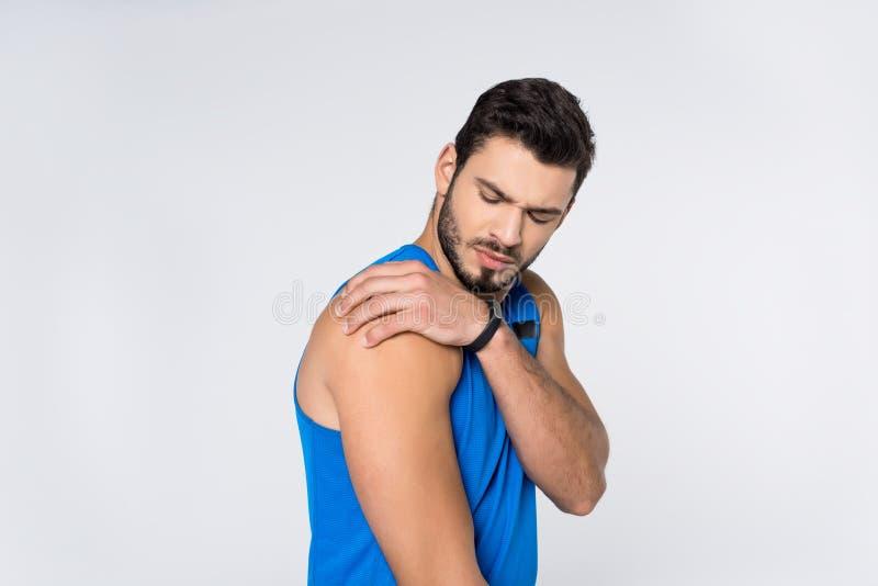 junger Mann mit den Schmerz in der Schulter lizenzfreies stockbild