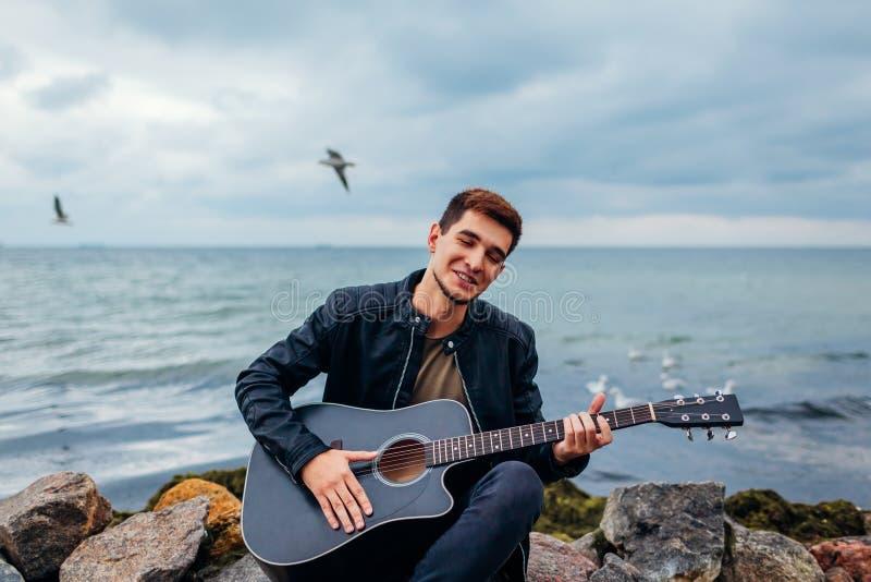 Junger Mann mit der Akustikgitarre, die auf dem Strand umgeben mit Rock am regnerischen Tag spielt und singt stockbild