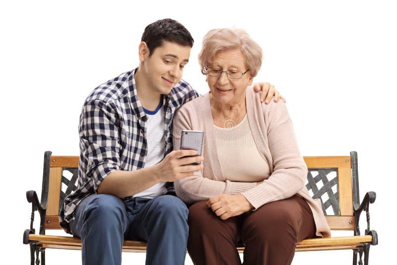 Junger Mann mit der reifen Frau, die ihr etwas am Telefon zeigt lizenzfreie stockfotos
