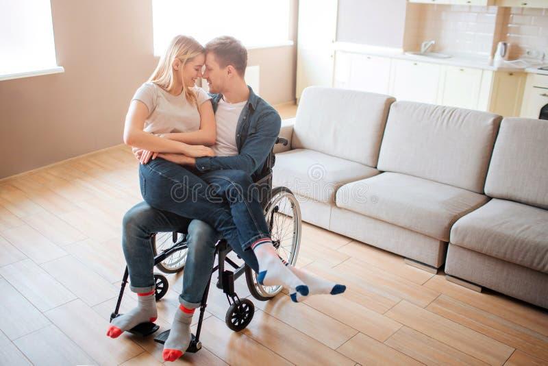 Junger Mann mit der Unfähigkeit und speziellem Bedarf, die Freundin auf Knien halten Sie lehnen sich miteinander und Lächeln re stockfotos