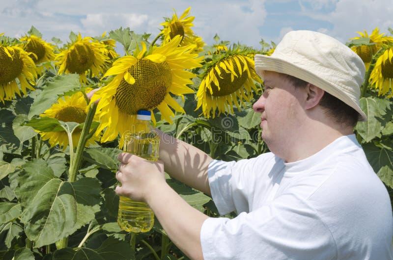 Junger Mann mit Down-Syndrom als Landwirtholdingflasche Sonnenblumenöl Schönes Sonnenblumenfeld stockbild
