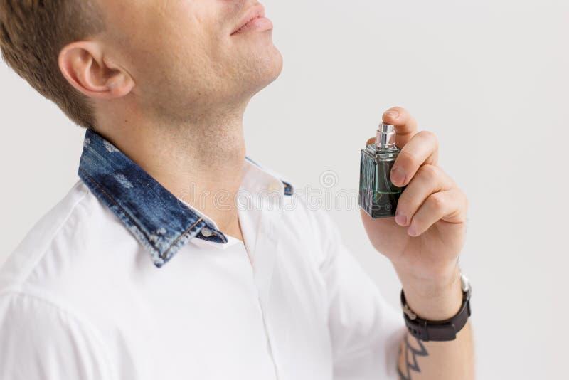 Junger Mann mit Duftstoffflasche stockfotos