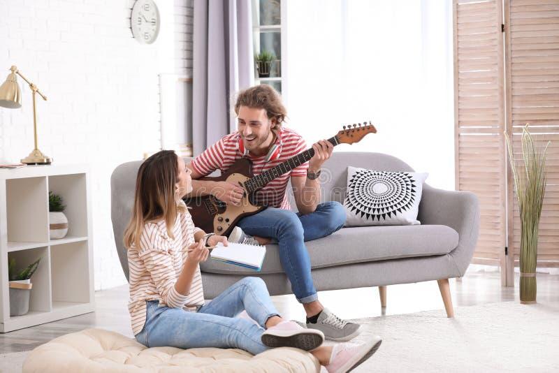 Junger Mann mit E-Gitarre und seinem verfassenden Lied der Freundin lizenzfreies stockbild