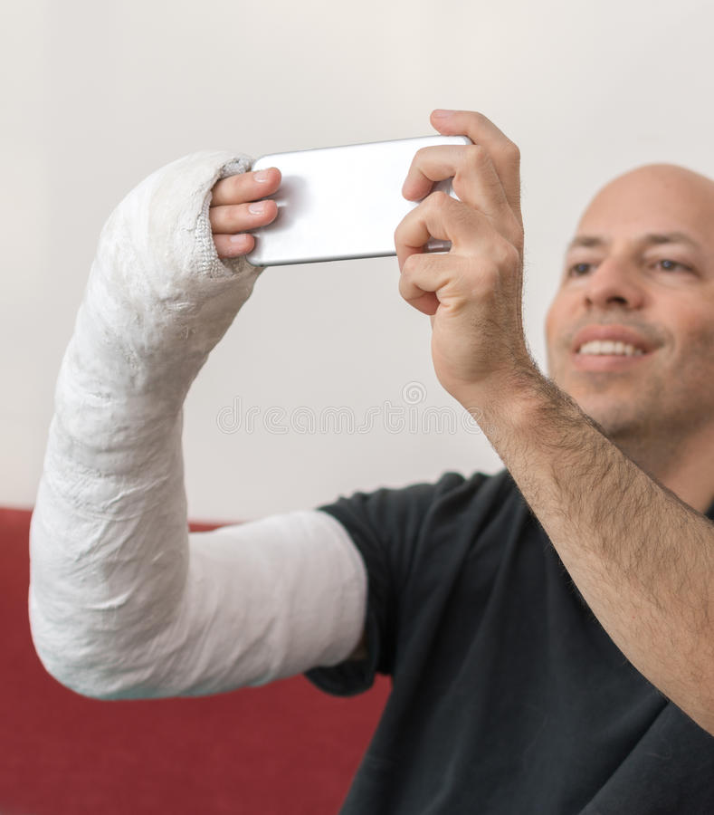 Junger Mann mit einem Arm warf das Nehmen eines selfie lizenzfreie stockfotos