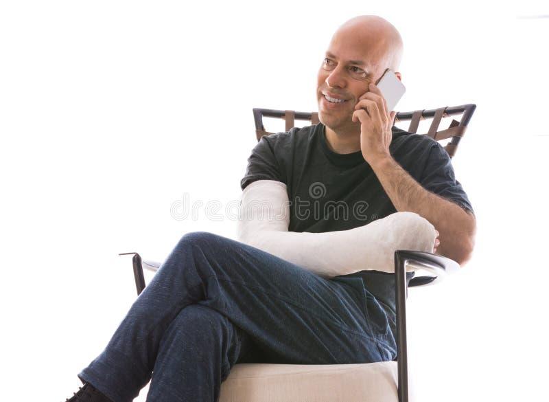 Junger Mann mit einem Arm warf die Unterhaltung an seinem Telefon stockbild