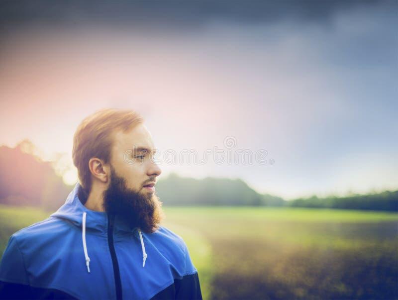 Junger Mann mit einem Bart, der einen Matrosen trägt und im Profil gegen grünes Feld und Himmel lizenzfreie stockfotos