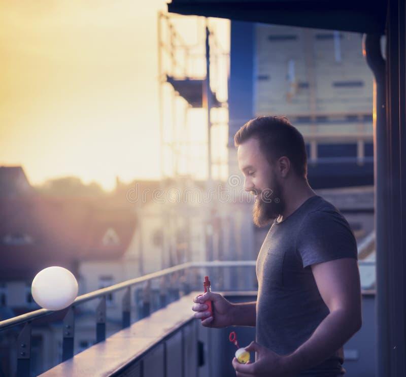 Junger Mann mit einem Bart, der Seifenblasen mithilfe der Zerstäuber gegen die Abendstadtlandschaft verwischt macht lizenzfreies stockfoto