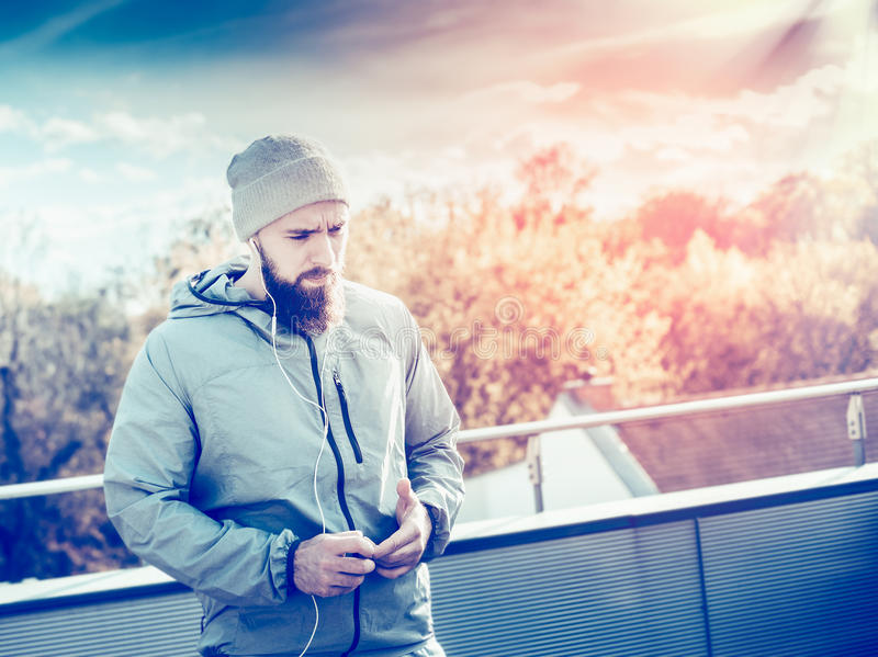 Junger Mann mit einem Bart, einen grauen Trainingsnazug tragend und stehen auf der Terrasse des Hauses, auf Hintergrund von Sonne stockbild