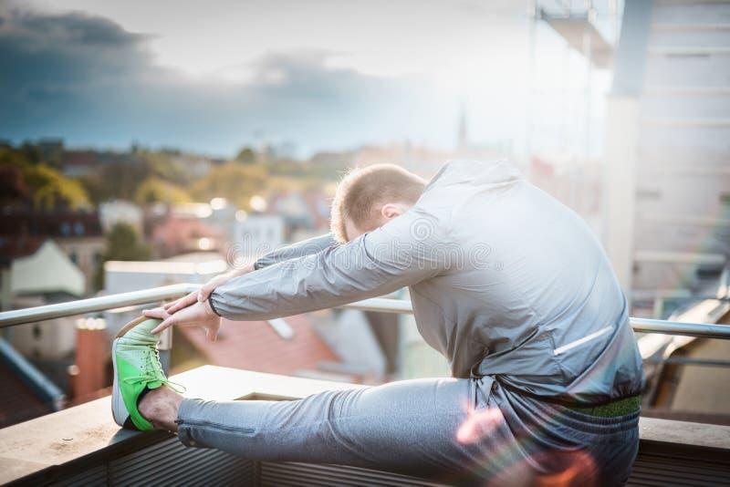 Junger Mann mit einem Bart in einer Trainingsjacke, stehendes Profil gegen unscharfe sonnige Landschaft stockbild