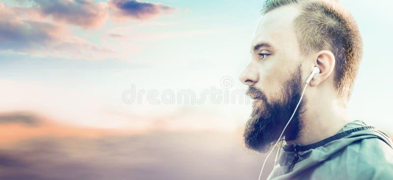 Junger Mann mit einem Bart in einer Trainingsjacke, stehendes Profil gegen unscharfe sonnige Landschaft lizenzfreie stockfotos