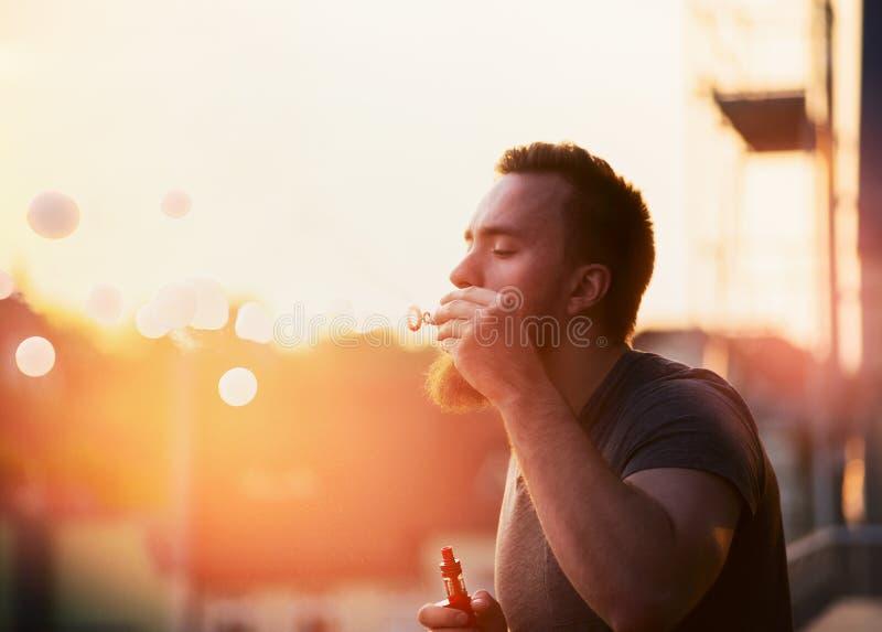 Junger Mann mit einem Bart macht die Blase mit dem Dampf nach innen und schafft weichen Hintergrund der Stadtlandschaft stockfotos